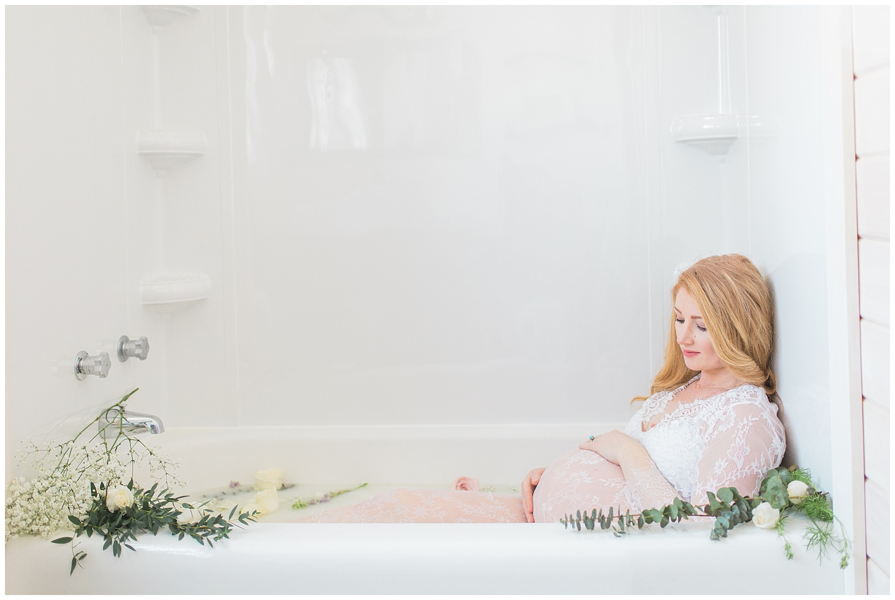 redheaded pregnant woman takes a milk bath with flowers in her bangor, maine, home in a white, see-through dress